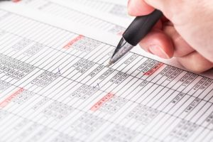 man checking of numbers on a spread sheet